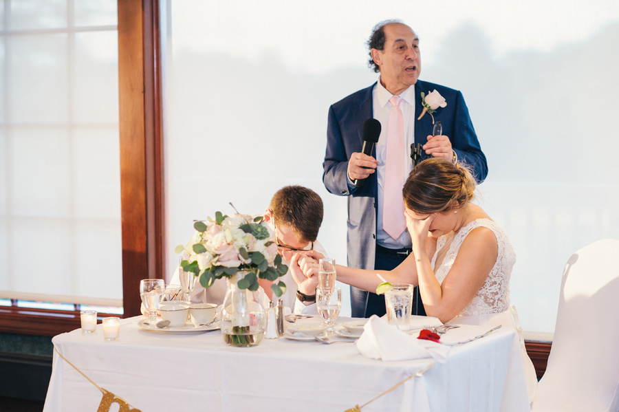 groom's father giving a blessing while couple bows heads at reception