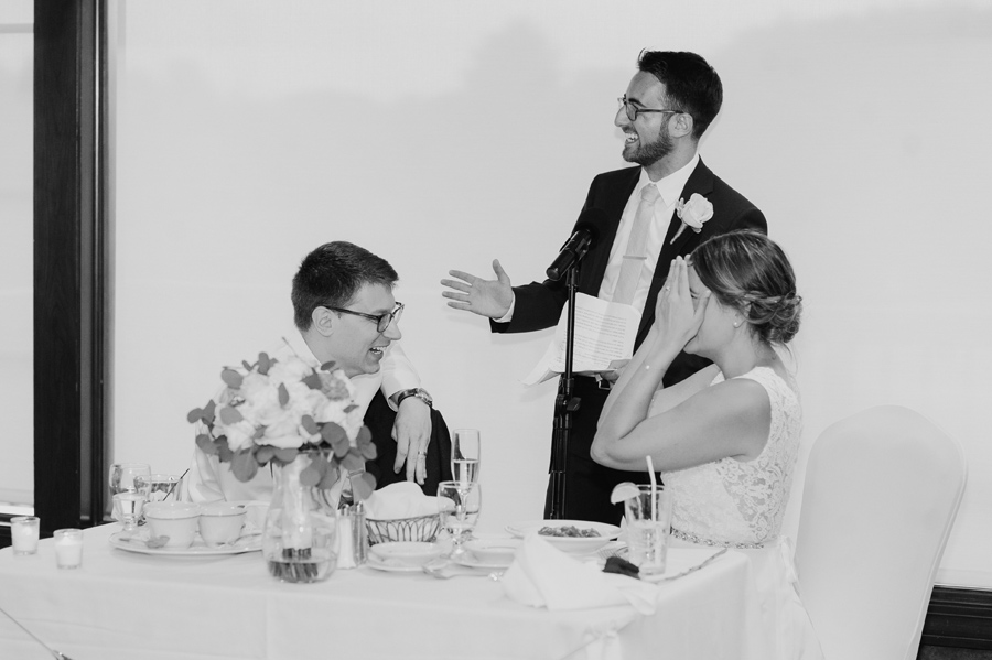 black and white of best man giving a speech while bride and groom laugh