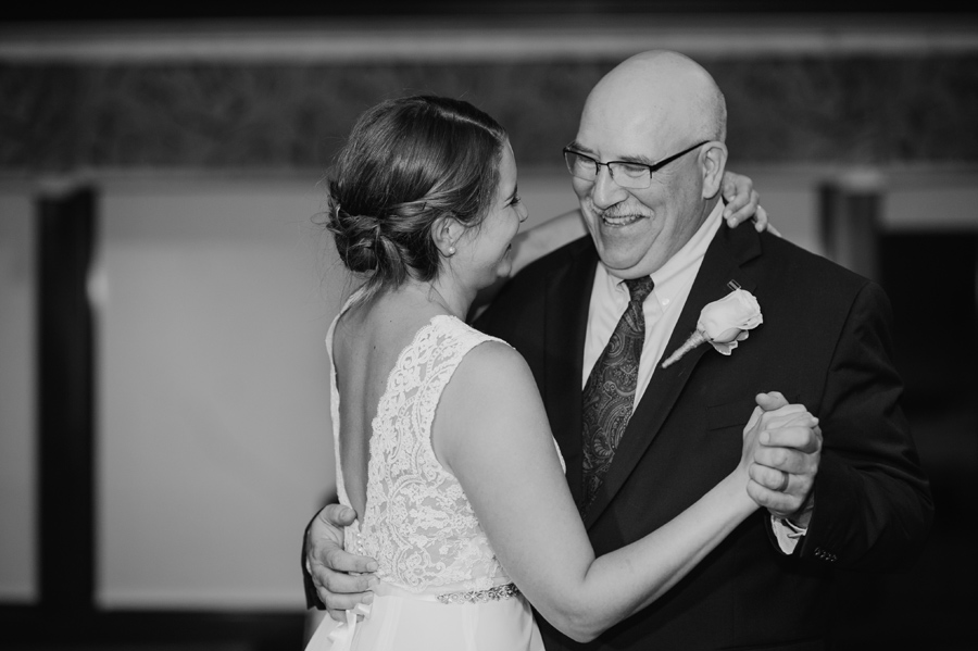 black and white of bride and her father smiling during the father daughter dance