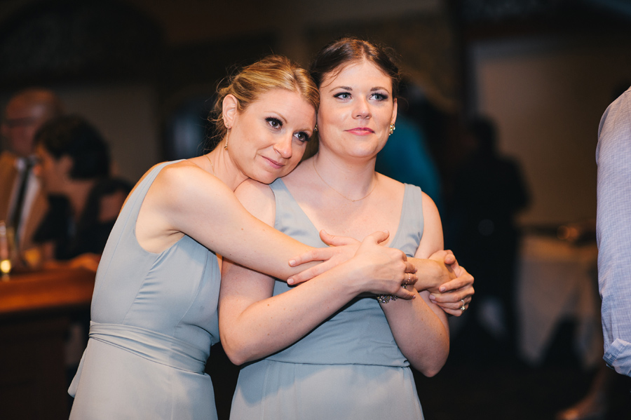 bridesmaids embracing and watching the father daughter dance with sentimental looks
