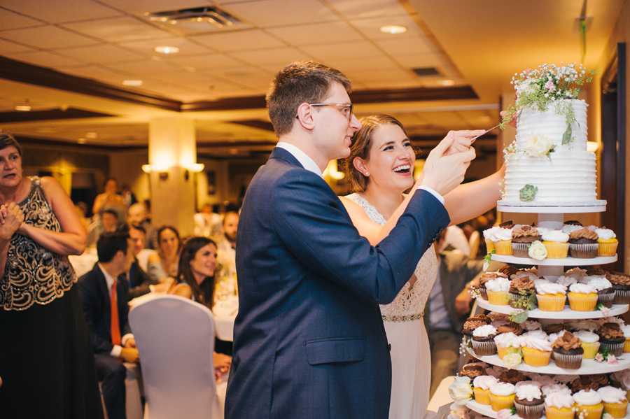 bride and groom cutting the two tier cake sitting atop a tower of cupcakes