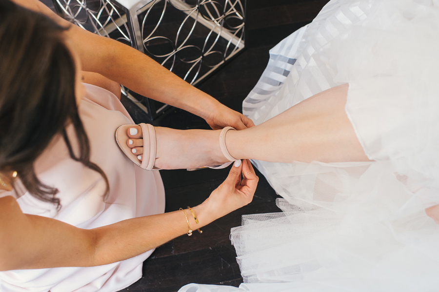 a bridesmaid helping the bride with her shoes