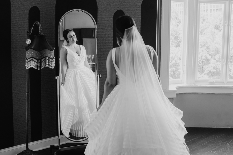 black and white of the bride smiling at herself in a full length mirror