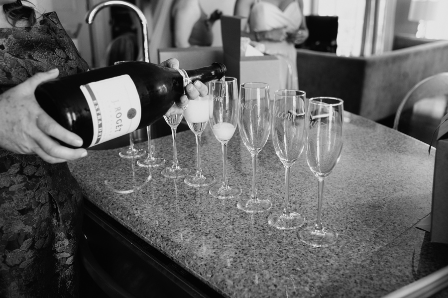 black and white pouring champagne into glass flutes with names engraved on them