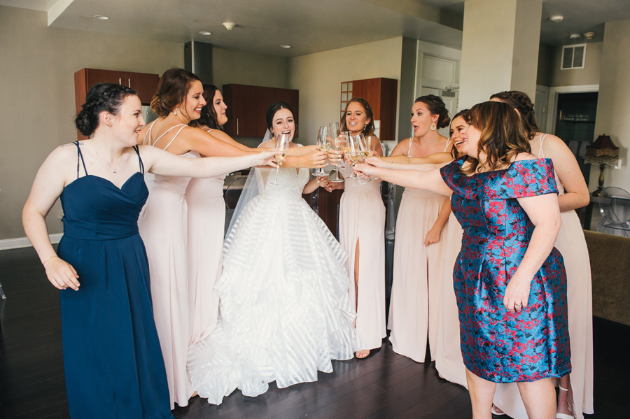 bride and bridal party doing a champagne toast cheers