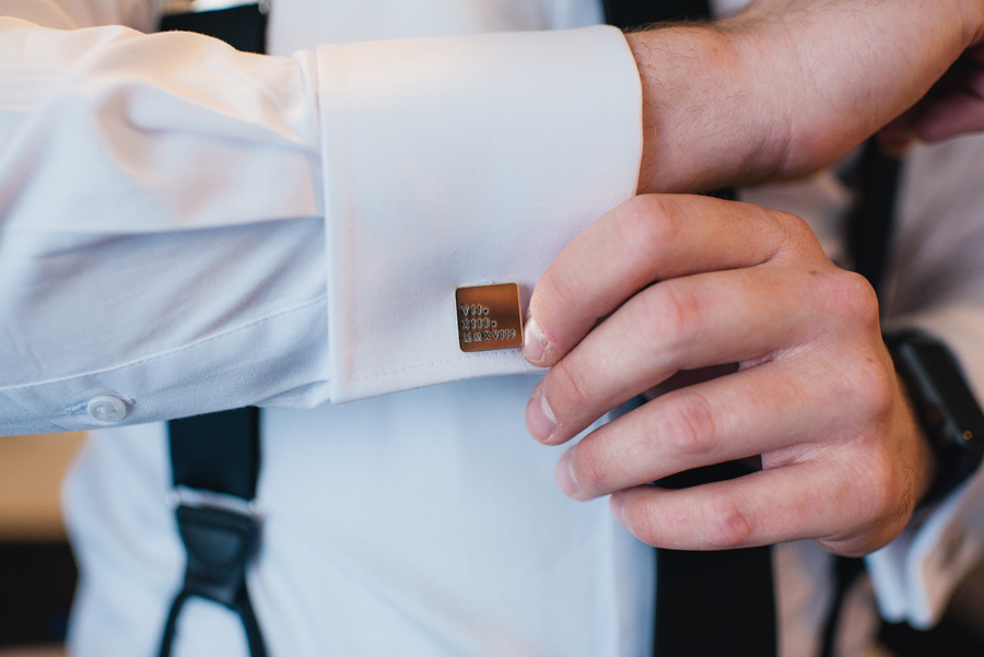 close up shot of the groom's custom made cuff links with the wedding day in roman numerals