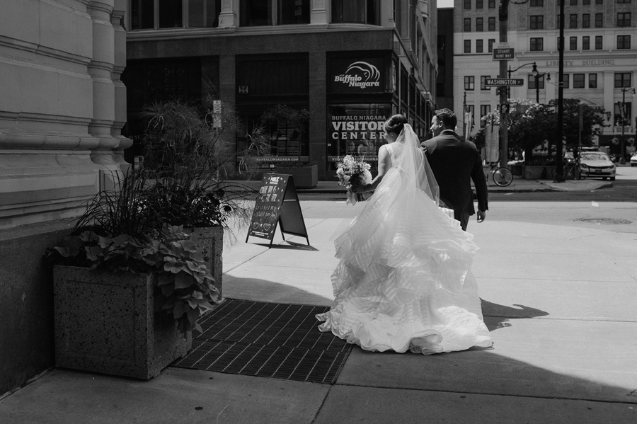 black and white of the bride and groom walking away from the camera around a corner on the street