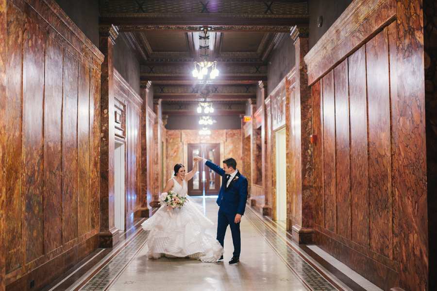 groom twirling his bride around in their hotel's hallway