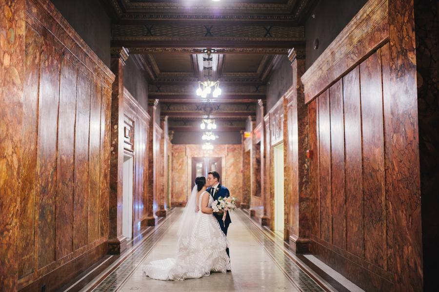 bride and groom kissing in the hallways of their wedding venue