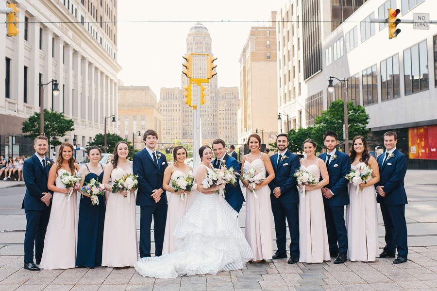 bridal party lined up on the street and smiling at the camera