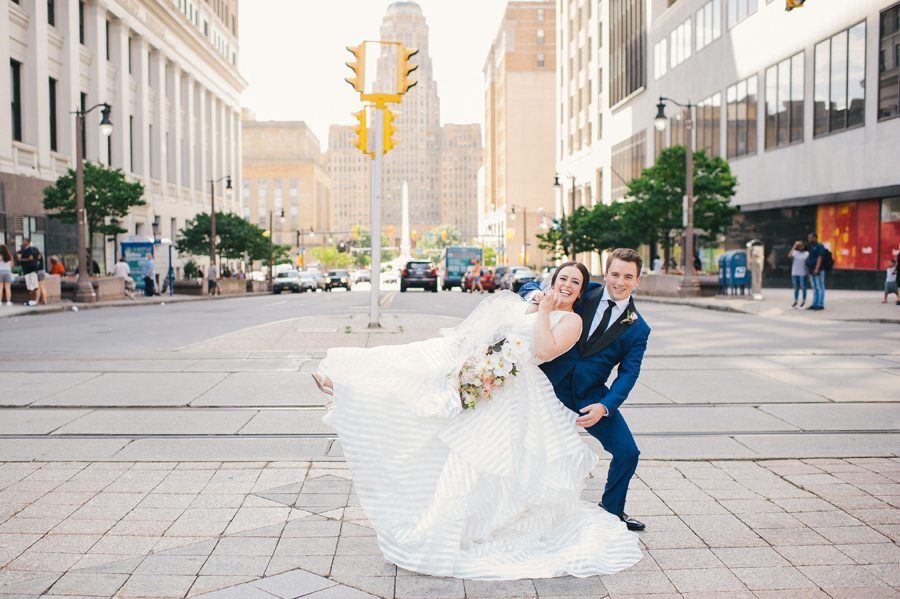 bride leaning into the groom with her leg in the air in the middle of a city street
