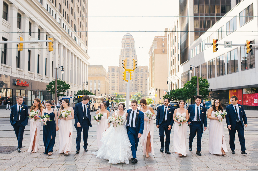 wedding party happily laughing and talking as they walk towards the camera on a brick paved street