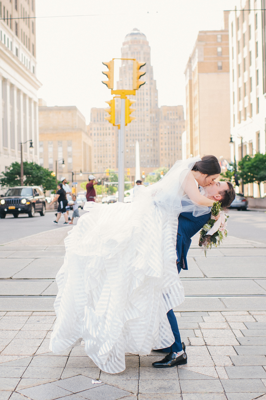 groom lifting and kissing bride under a traffic light