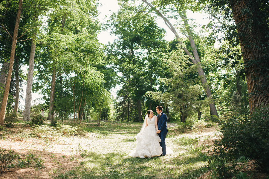 bride leaning into groom and smiling in a wooded area