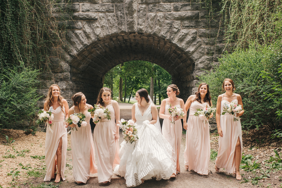 bridal party laughing with each other and walking towards camera