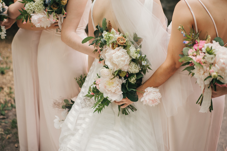detail shots of bouquets of blush, pink and white being held behind the backs of the bridal party