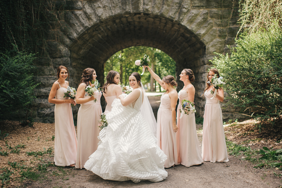 bride having fun with her dress and her bridesmaids