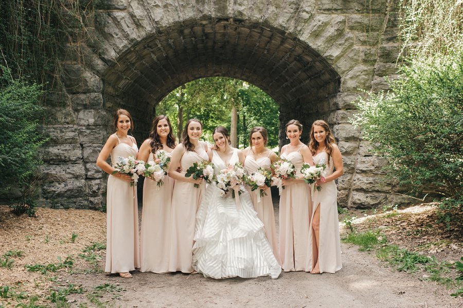 full length of bride and bridesmaids smiling for the camera