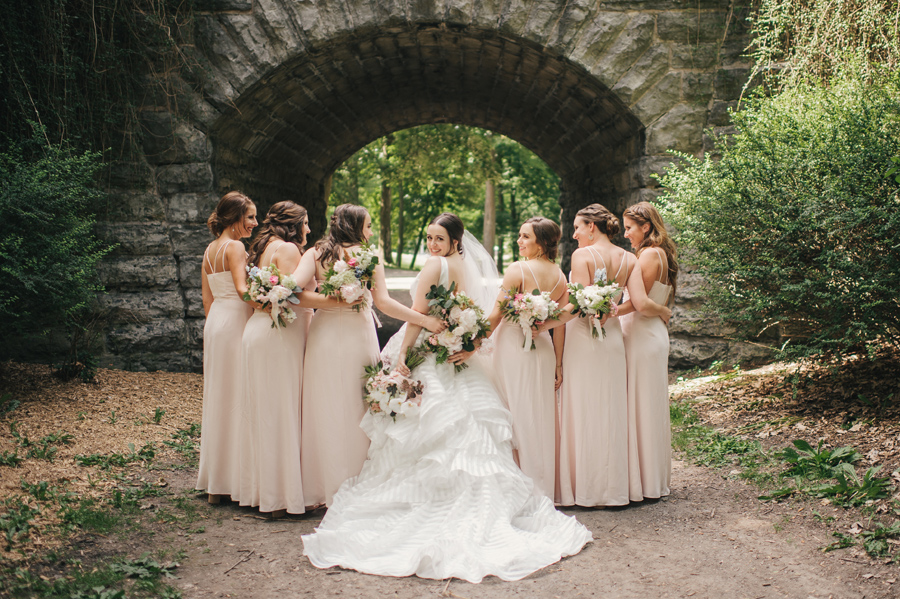 bridal party facing away from camera while bride looks back at camera over her shoulder and smiles