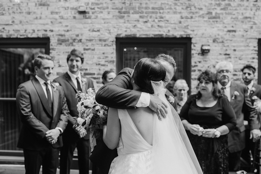 black and white of the father of the bride hugging her at the altar