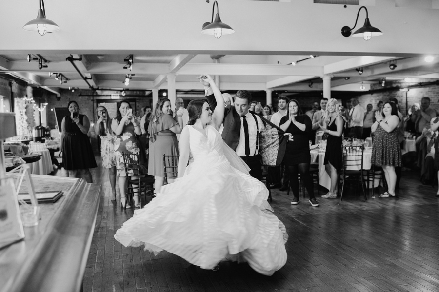 black and white of groom spinning the bride while they make their grand reception entrance