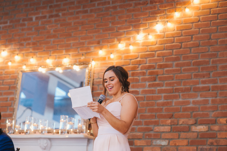 maid of honor smiling as she reads her speech during the wedding reception