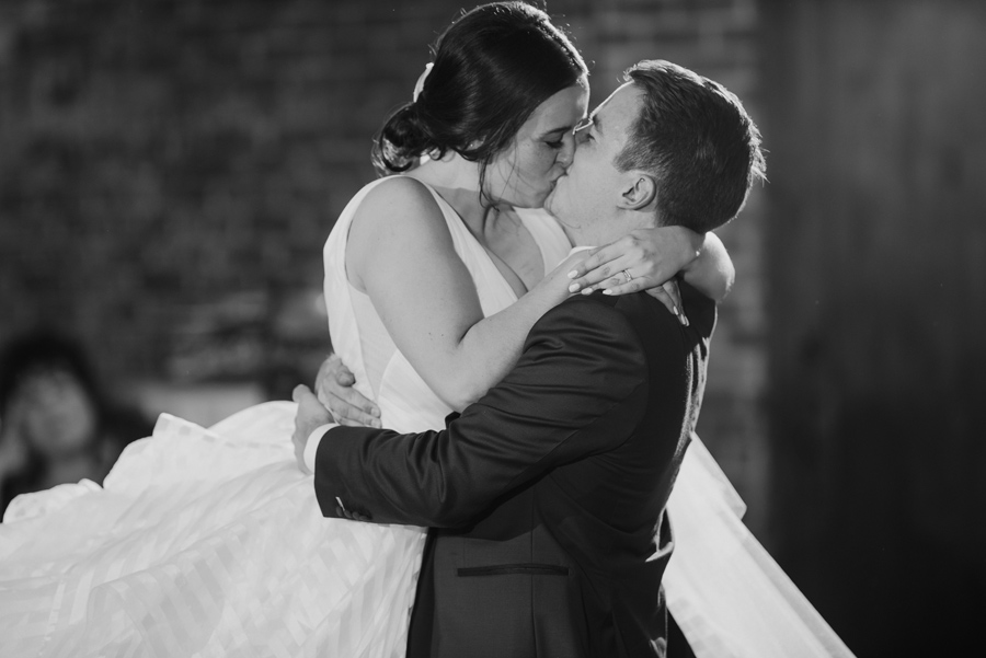 black and white of the groom lifting and kissing the bride during their first dance