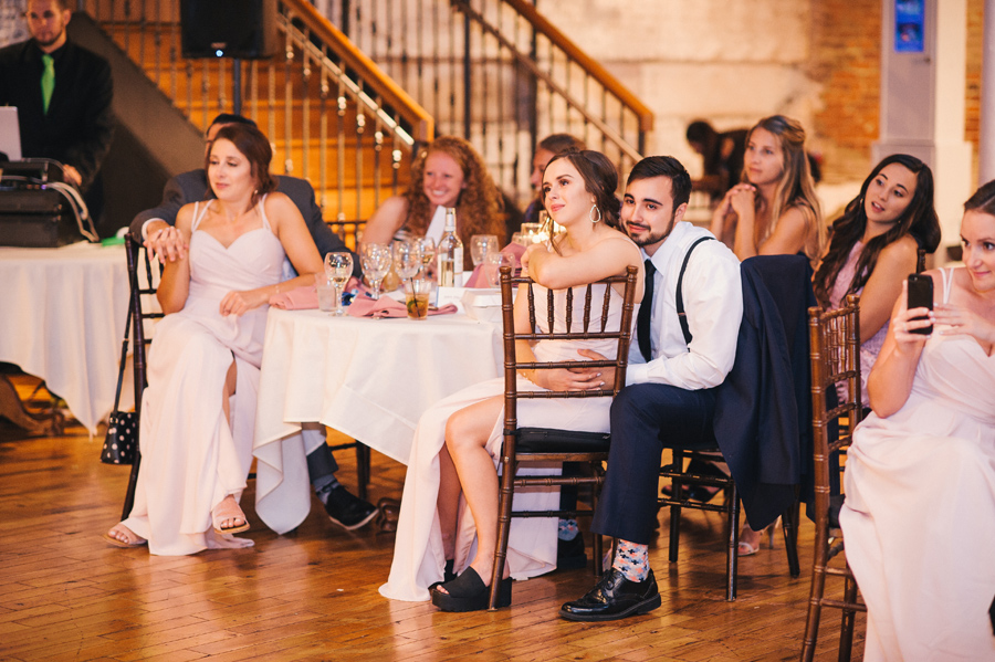 bridal party seated and smiling while watching the first dance