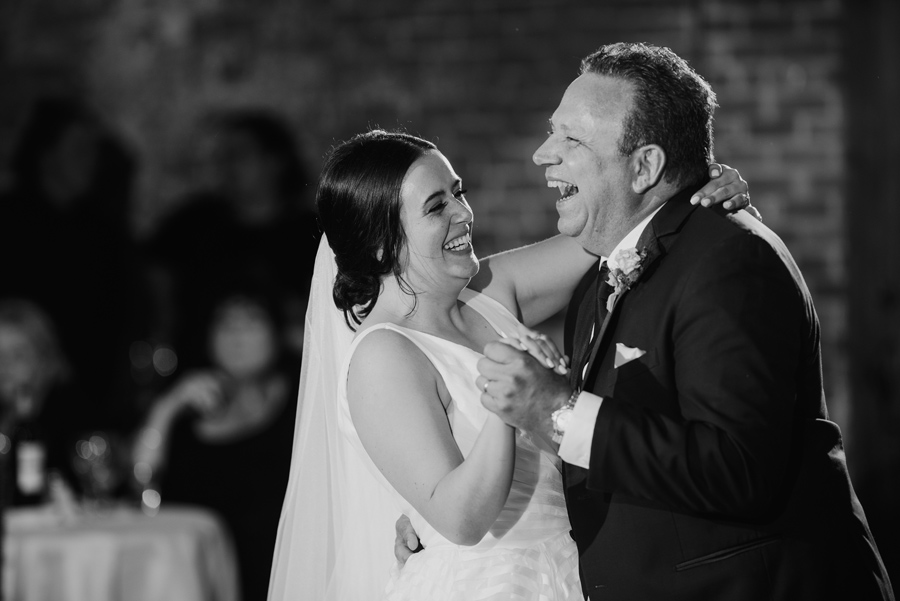 black and white of the bride and her father laughing together during their dance