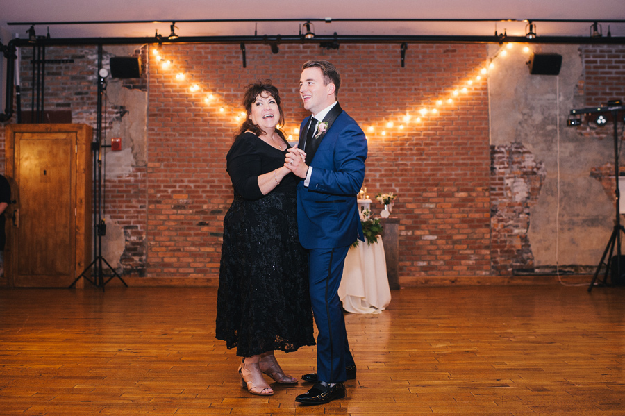 full length of the groom and his mother smiling during the mother son dance