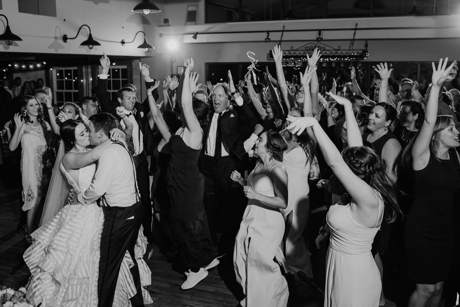 black and white of bride and groom kissing on the dance floor while wedding guest cheer around them