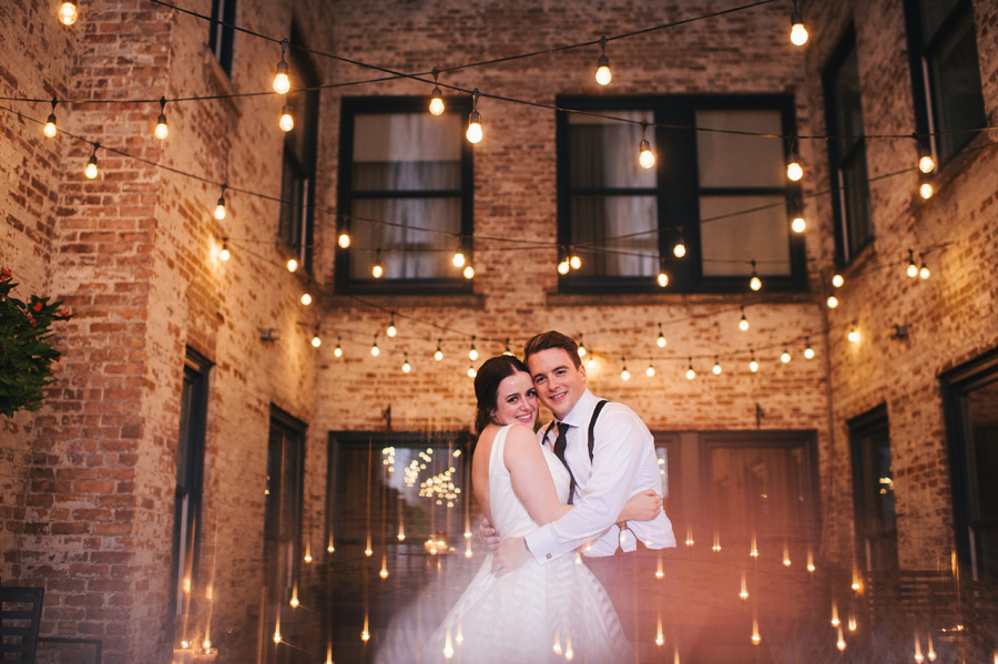 bride and groom holding each other close and smiling at the camera in the outdoor courtyard at night with many strands of twinkle lights