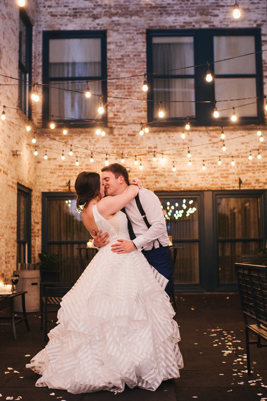 fill length of bride and groom leaning in for a kiss outdoors at night with twinkle lights in a brick wall courtyard