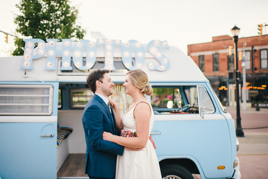 bride and groom smiling at each other in front of photo booth bus