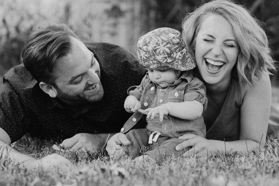 black and white close shot of family laying on stomachs in the grass laughing