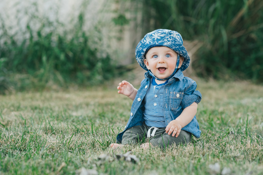 happy baby boy sitting in grass and smiling at camera