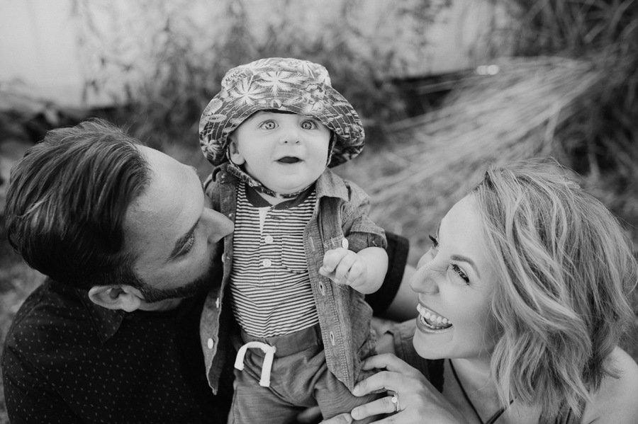 black and white close up of baby boy looking amazed and mom and dad laughing