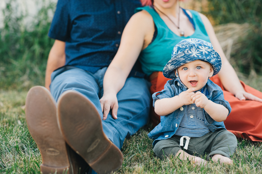 baby boy sitting in grass and looking coyly at camera with parents behind him