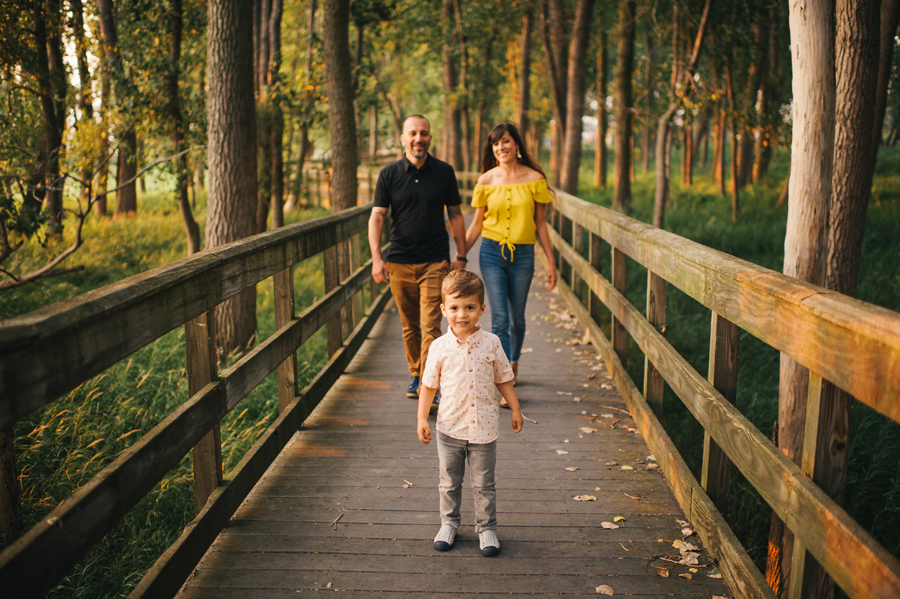 family walking on a bridge in the woods towards the camera