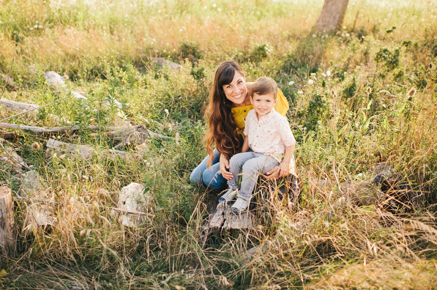 mom and son sitting on a log in a field smiling at camera