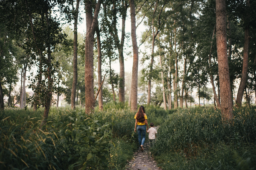 mom and son walking down a path through the woods headed away from camera