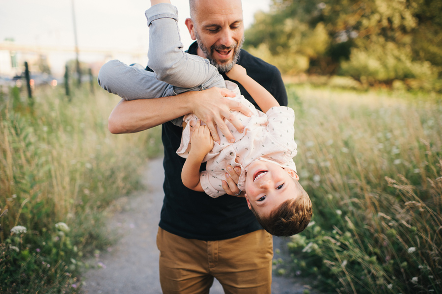 dad holding son upside down and laughing
