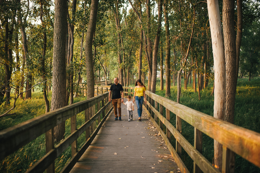 family holding hands and walking down a bridge towards camera